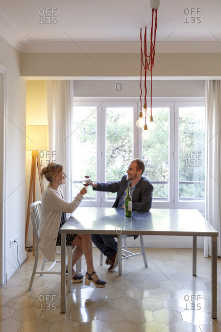 Mid adult couple relaxing at home, having glass of wine, making toast