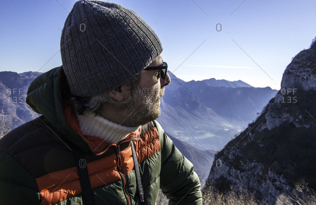 Man in rural setting, looking at mountain view, Italy