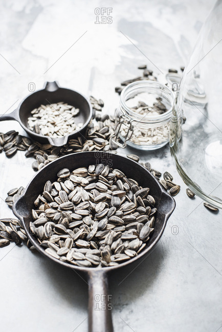 Studio shot, overhead view of sunflower seeds in pans and jars
