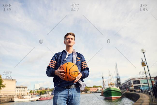 Young man near river, holding basketball, Bristol, UK