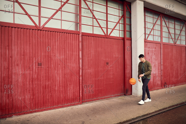 Young man in urban area, bouncing basketball, Bristol, UK