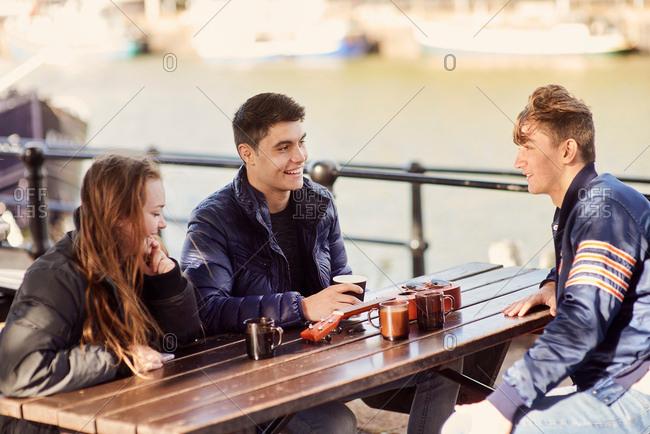 Three friends sitting outdoors, drinking hot drinks, Bristol, UK