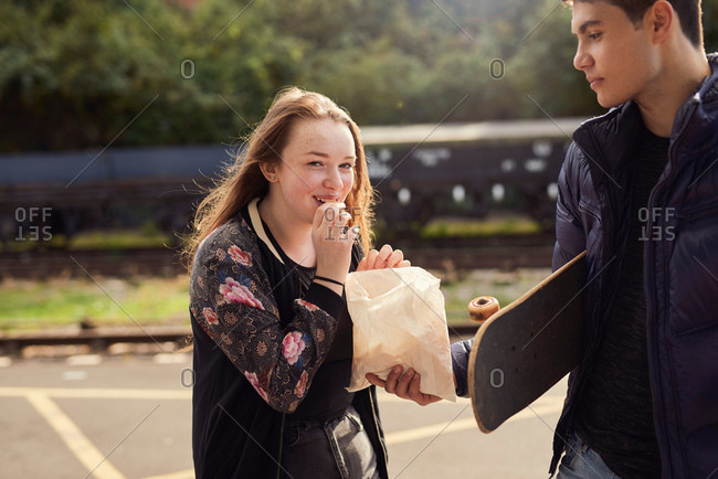 Young man sharing bag of chips with young woman,  skateboard under young man's arm, Bristol, UK