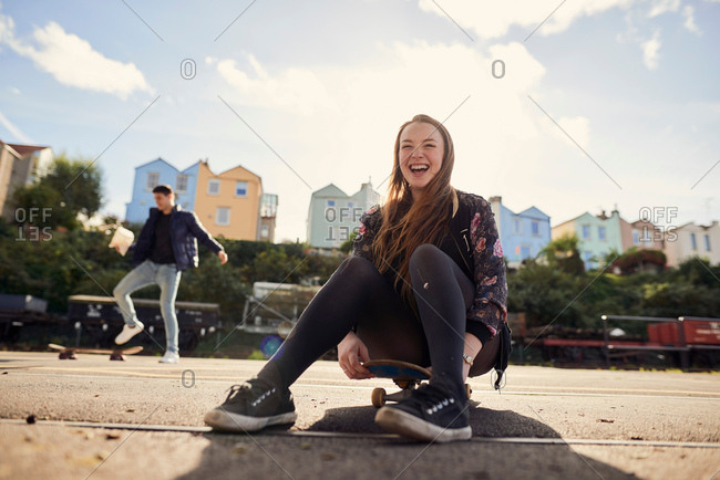 Two friends fooling around outdoors, young woman sitting on skateboard, laughing, Bristol, UK