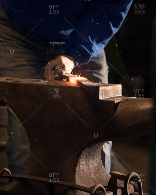 Farrier forging horseshoe on anvil