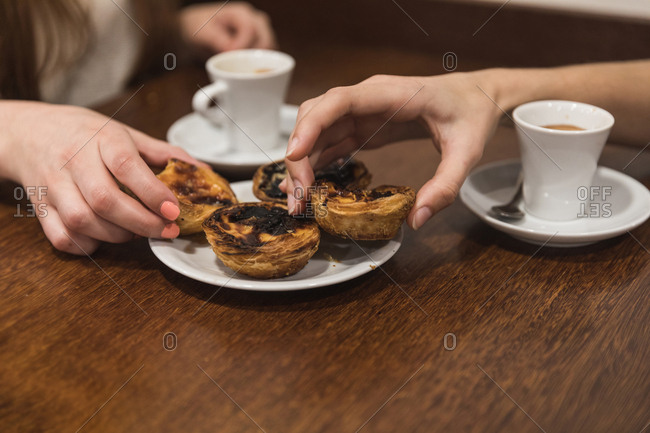 Cropped view of friends picking pastries from plate