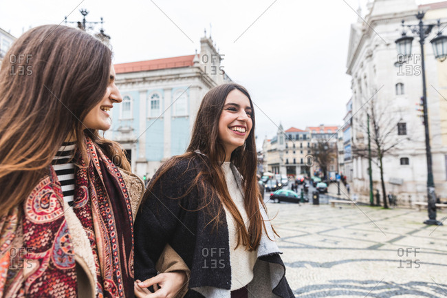 Woman walking arm and arm in city, Lisbon, Portugal