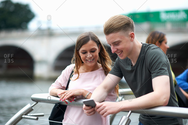 Young man and woman beside river, looking at smartphone