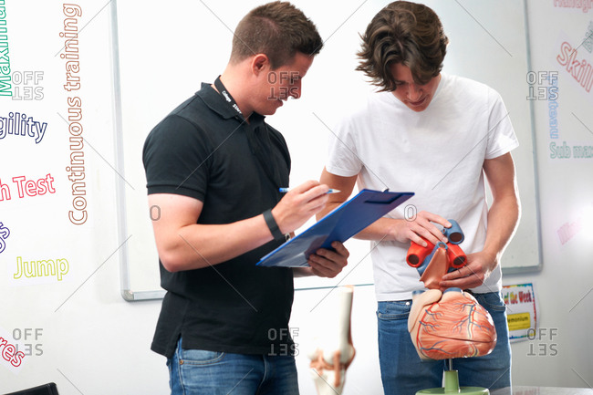 Male student holding model heart valves, being assessed by tutor in biology class