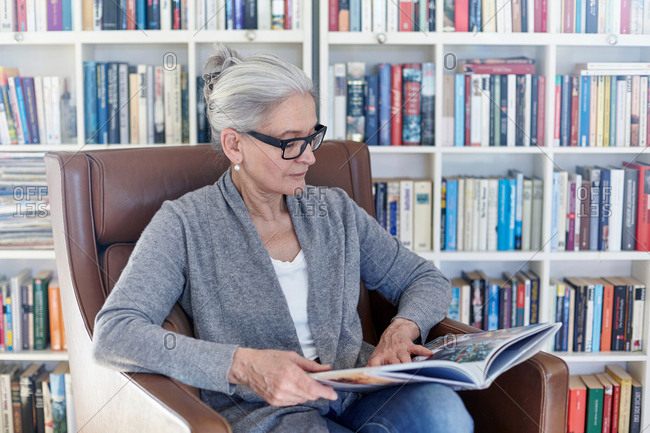 Senior woman sitting in chair in library, reading book