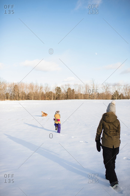 Kids and dogs playing in snow-covered field, Lakefield, Ontario, Canada