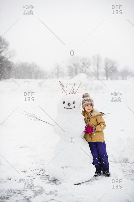 Girl shovelling snow in front of snowman, Lakefield, Ontario, Canada