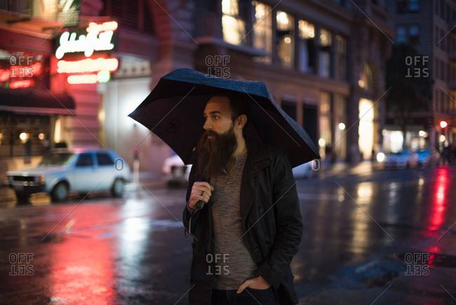 Mid adult man walking in city at night, using umbrella, Downtown, San Francisco, California, USA