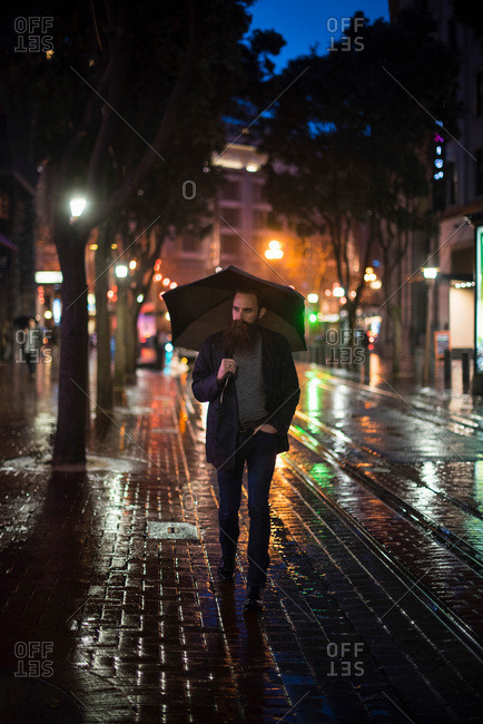 Mid adult man walking in city at night, using umbrella, Downtown, San Francisco, California, USA