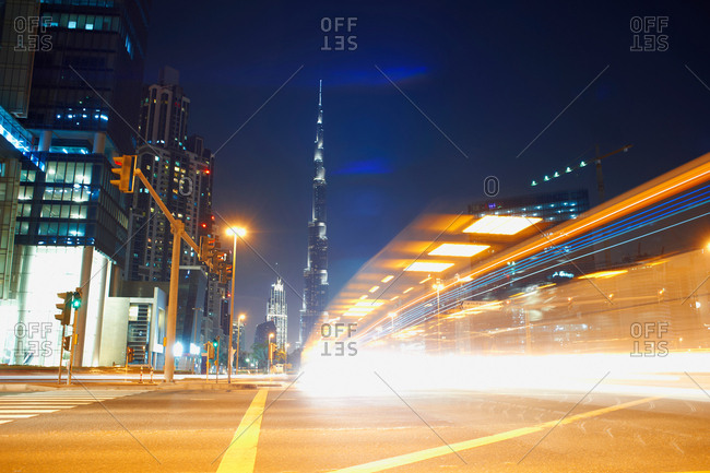 Cityscape at night showing Burj Khalifa in background and light trails, Dubai, UAE
