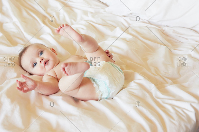 Portrait of cute blue eyed baby girl in diaper lying on bed