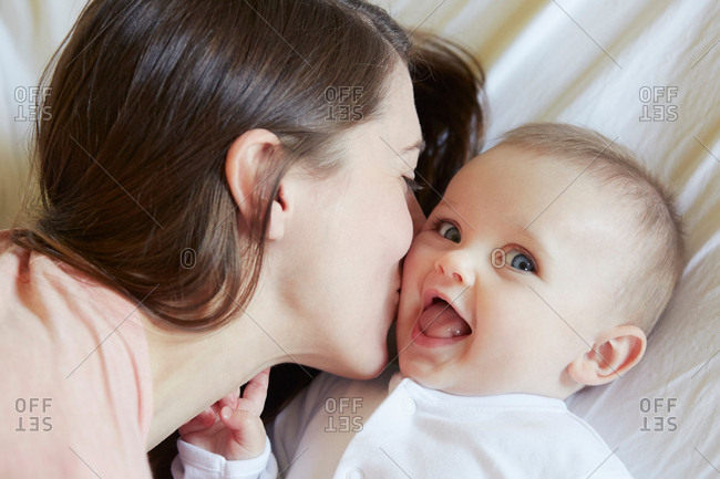 Portrait of cute baby girl being kissed by mother on bed