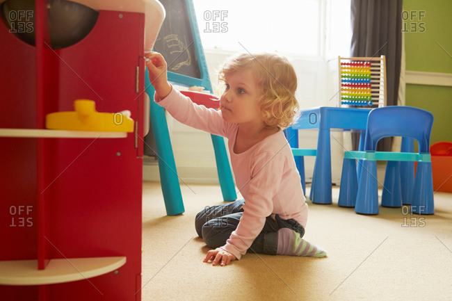 Female toddler playing on playroom floor