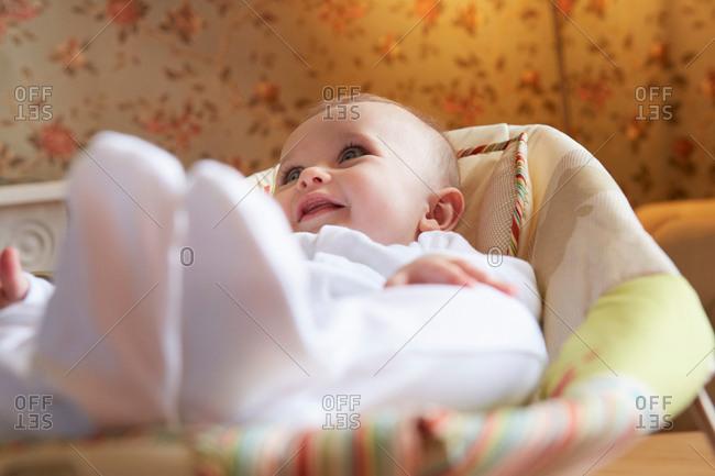 Baby girl lying on baby bouncer chair in nursery