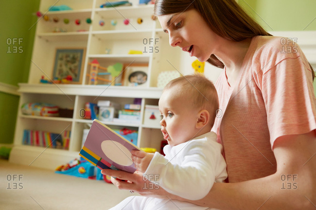 Mid adult woman and baby daughter reading storybook in playroom