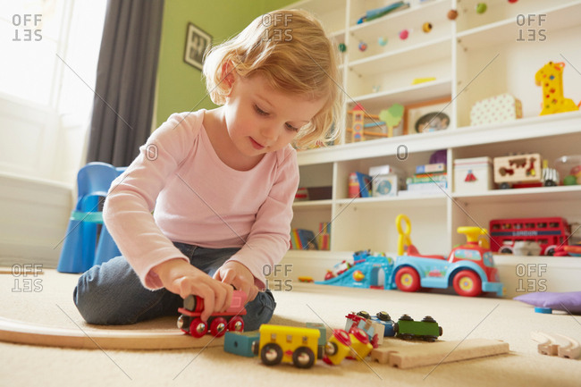 Female toddler playing with toy train on playroom floor