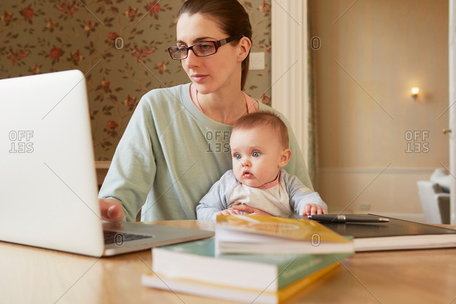 Baby girl sitting on mother's lap staring at laptop