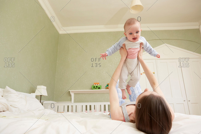 Women lying on bed holding up baby daughter