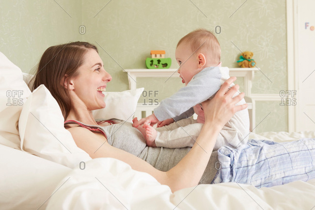 Women lying on bed playing with baby daughter