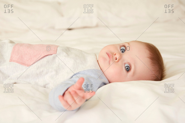 Portrait of blue eyed baby girl lying on bed