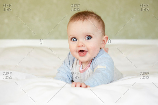 Portrait of cute blue eyed baby girl lying on bed
