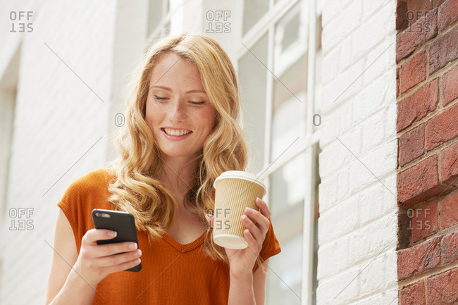 Woman having coffee and texting in street, London, UK