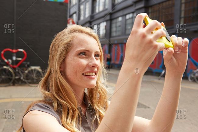 Woman taking selfie in street, London, UK