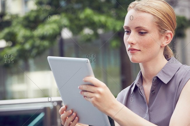 Woman using digital tablet, London, UK