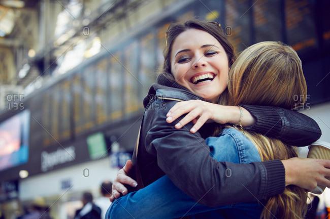 Women hugging in train station concourse, London, UK