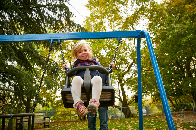 Father pushing daughter on playground swing