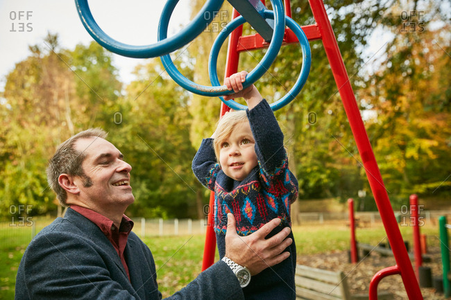 Father helping daughter on monkey bars in playground