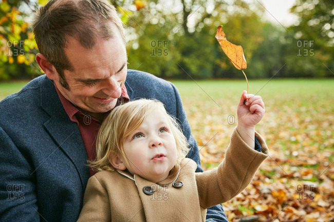 Daughter sitting on father\'s lap holding autumn leaf
