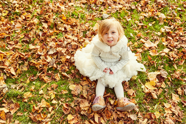 Portrait of girl sitting in autumn leaves looking at camera smiling