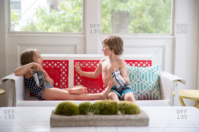 Boy and girl on conservatory sofa with packets of crisps