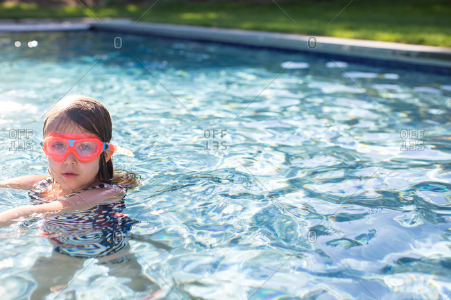 Portrait of girl in pink swimming goggles in outdoor swimming pool