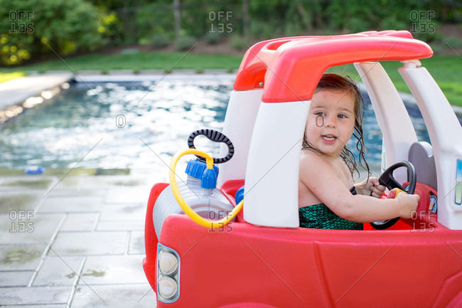 Girl driving toy car by outdoor swimming pool
