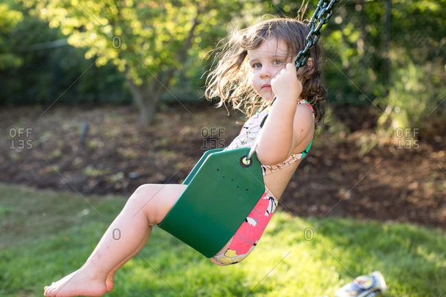 Girl swinging on garden swing