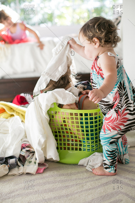 Female toddler removing laundry from child hiding in laundry basket