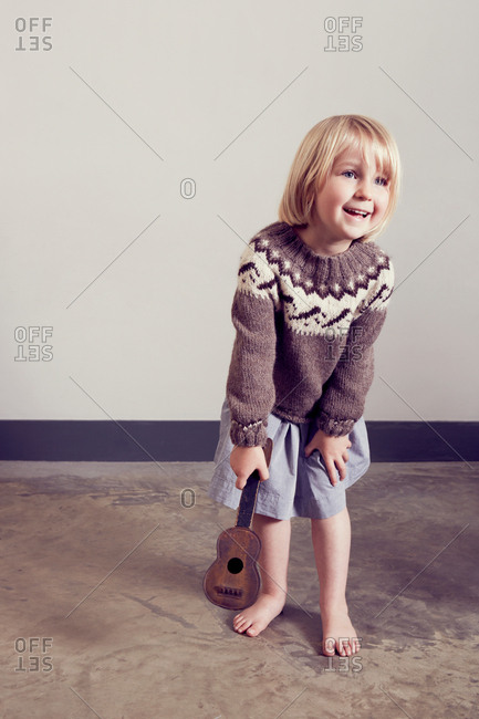 Girl playing with old wooden toy guitar