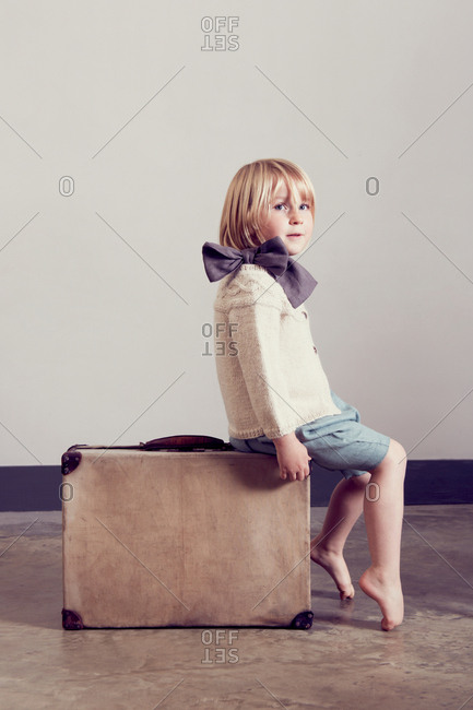 Girl in tied bow sitting on vintage suitcase