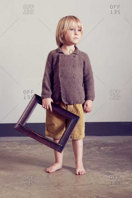 Girl holding empty picture frame gazing
