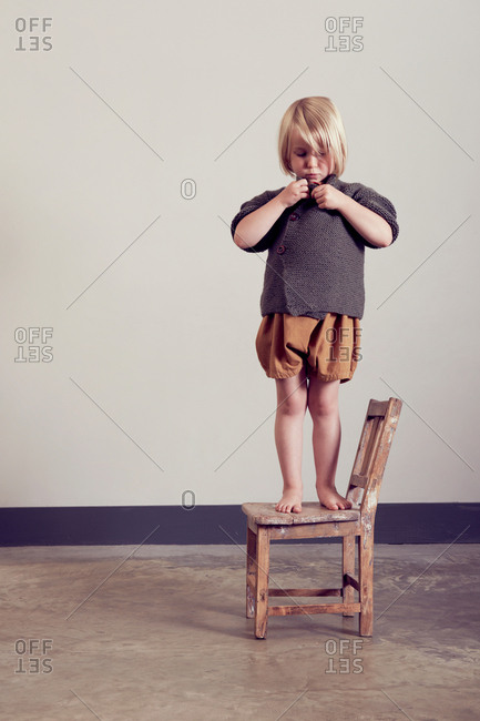 Girl standing on old wooden chair fastening cardigan button