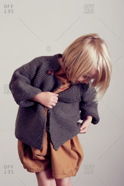 Girl examining hand knitted cardigan
