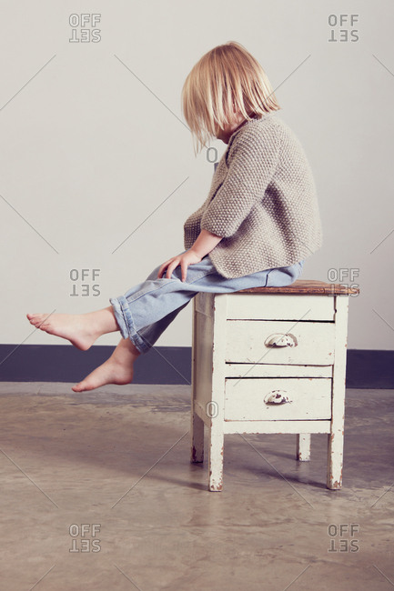 Blond girl sitting on old cabinet looking down