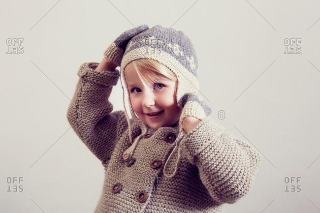 Portrait of girl adjusting hand knitted hat